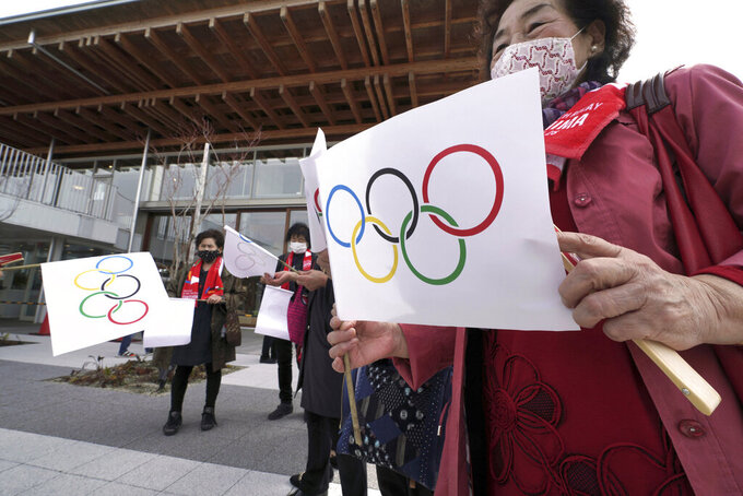 Local residents carry handmade flags featuring Olympic Rings at the torch relay route of the first section of the Fukushima Torch Relay in Naraha, Fukushima prefecture, northeastern Japan, Thursday, March 25, 2021. The torch relay for the postponed Tokyo Olympics began its 121-day journey across Japan on Thursday and is headed toward the opening ceremony in Tokyo on July 23. (AP Photo/Eugene Hoshiko)