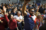 Protesters chant slogans during ongoing protests against the Lebanese political class, as riot police stand guard in front of a Finance Ministry building in Beirut, Lebanon, Friday, Nov. 29, 2019. Protesters have been holding demonstrations since Oct. 17 demanding an end to widespread corruption and mismanagement by the political class that has ruled the country for three decades. (AP Photo/Bilal Hussein)