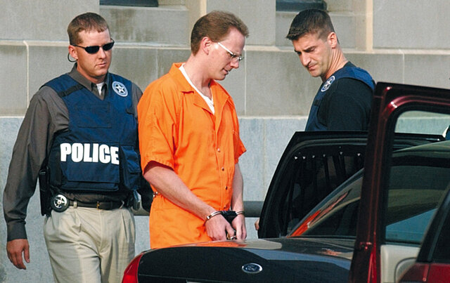 FILE - In this Aug. 18, 2004 file photo, Dustin Honken is led by federal marshals to a waiting car after the second day of jury selection in federal court in Sioux City, Iowa.  A federal judge has denied the Iowa drug kingpin's requests to delay his execution, which is scheduled for Friday, July 17, 2020. U.S. District Judge Leonard Strand wrote Tuesday, July 14 that he would not intervene to delay Honken's execution date due to the coronavirus pandemic. He said the Bureau of Prisons was in the best position to weigh the health risks against the benefits of carrying out the execution.   (Tim Hynds/Sioux City Journal via AP, File)