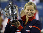 FILE - In this Sept. 13, 2009, file photo, Kim Clijsters holds the trophy after winning the women's championship over Caroline Wozniacki, at the U.S. Open tennis tournament in New York. Four-time Grand Slam champion Kim Clijsters is planning another comeback. A mother of three, the Belgian who retired after the 2012 U.S. Open wants a new challenge, she told the WTA in an interview on its website on Thursday, Sept. 12, 2019. (AP Photo/Charles Krupa, FIle)