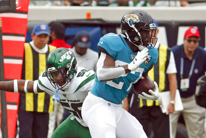Jacksonville Jaguars running back Leonard Fournette, right, breaks a tackle by New York Jets linebacker James Burgess, left, for a long run during the first half of an NFL football game, Sunday, Oct. 27, 2019, in Jacksonville, Fla. (AP Photo/Stephen B. Morton)