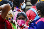 A family wearing face masks to prevent the spread of the coronavirus wait for a bus in Kolkata, India, Friday, Oct. 30, 2020. Health officials have warned about the potential for the coronavirus to spread during the upcoming religious festival season, which is marked by huge gatherings in temples and shopping districts. (AP Photo/Bikas Das)