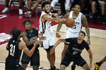 San Antonio Spurs' Nate Renfro, center, passes against the Brooklyn Nets during the first half of an NBA summer league basketball game Sunday, Aug. 15, 2021, in Las Vegas. (AP Photo/John Locher)