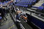 Personel remove the balls from the playing court after the NCAA college basketball games were canceled at the Atlantic Coast Conference tournament in Greensboro, N.C., Thursday, March 12, 2020. (AP Photo/Gerry Broome)