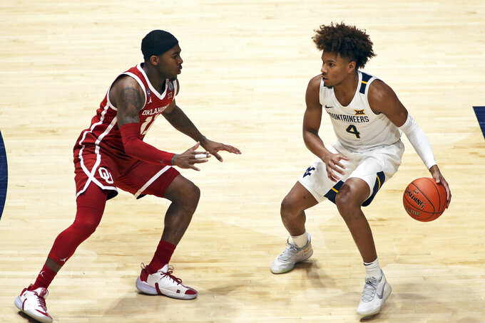West Virginia guard Miles McBride (4) looks for an outlet as Oklahoma guard De'Vion Harmon (11) defends during the first half of an NCAA college basketball game Saturday, Feb. 13, 2021, in Morgantown, W.Va. (AP Photo/Kathleen Batten)