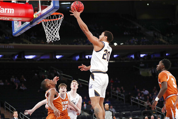California guard Matt Bradley (20) goes up for a layup as Texas guard Matt Coleman III, far left, Texas center Will Baker (50) and California forward Lars Thiemann (21) watch from the floor during the first half of an NCAA college basketball game in the 2K Empire Classic, Friday, Nov. 22, 2019, in New York. Texas guard Courtney Ramey (3) is at far right.(AP Photo/Kathy Willens)