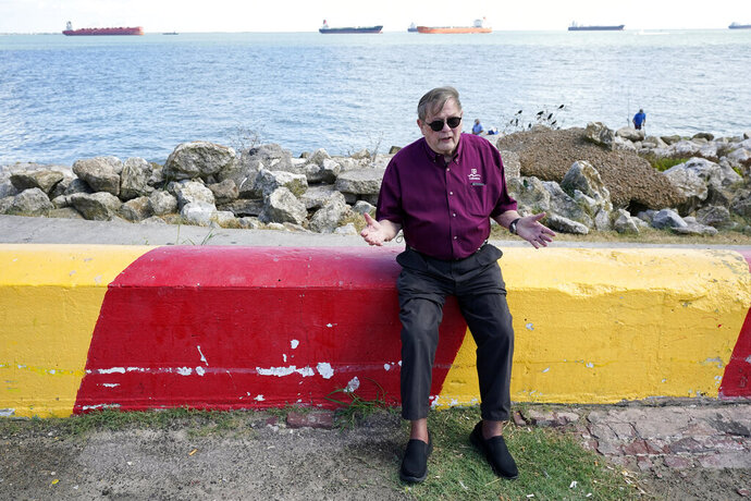 Bill Merrell, a professor in the Marine Sciences Department at Texas A&M University at Galveston and a former president of the school, sits along Galveston Bay as he talks about the Ike Dike project Friday, Sept. 4, 2020, in Galveston, Texas. The Ike Dike is a coastal barrier that, when completed, would protect the Houston-Galveston region including Galveston Bay from hurricane storm surge. The project was conceived by Merrell in response to the extensive surge damage caused by Hurricane Ike in September of 2008. (AP Photo/David J. Phillip)