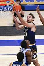 Notre Dame's Nikola Djogo (13) collides with Pittsburgh's Xavier Johnson (1) as he shoots during the second half of an NCAA college basketball game, Saturday, Jan. 30, 2021, in Pittsburgh. (AP Photo/Keith Srakocic)