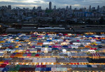 Tents of food stalls and other vendors are illuminated at Rot Fai Market in Bangkok, Thailand, Friday, June 19, 2020. Daily life in the capital resumes to normal as the government continues to ease restrictions related to running business and activities that were imposed weeks ago to combat the spread of COVID-19. Thailand reported no local transmissions of the coronavirus in the past 3 weeks. (AP Photo/Sakchai Lalit)