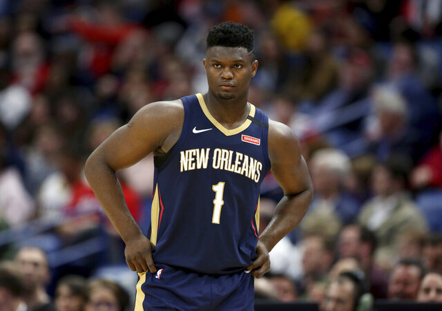 "FILE - In this March 6, 2020, file photo, New Orleans Pelicans forward Zion Williamson walks onto the court during the second half of the team's NBA basketball game against the Miami Heat in New Orleans. The rookie sensation's availability to play remained unclear as the season's resumption in Lake Buena Vista, Florida, approached. He left the NBA's so-called ""bubble"" setup on July 16 to attend to an unspecified family medical matter. A week later, the club had yet to provide an update on his possible return.  (AP Photo/Rusty Costanza, File)"