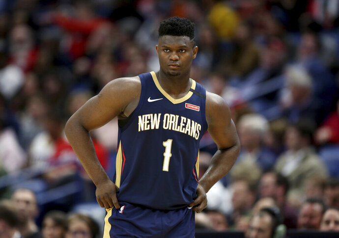 """FILE - In this March 6, 2020, file photo, New Orleans Pelicans forward Zion Williamson walks onto the court during the second half of the team's NBA basketball game against the Miami Heat in New Orleans. The rookie sensation's availability to play remained unclear as the season's resumption in Lake Buena Vista, Florida, approached. He left the NBA's so-called """"bubble"""" setup on July 16 to attend to an unspecified family medical matter. A week later, the club had yet to provide an update on his possible return.  (AP Photo/Rusty Costanza, File)"""