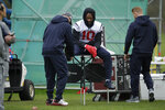 Houston Texans' wide receiver DeAndre Hopkins, 10, sits on a table during an NFL practice session at the London Irish rugby team training ground in the Sunbury-on-Thames suburb of south west London, Friday, Nov. 1, 2019. The Houston Texans are preparing for an NFL regular season game against the Jacksonville Jaguars in London on Sunday. (AP Photo/Matt Dunham)