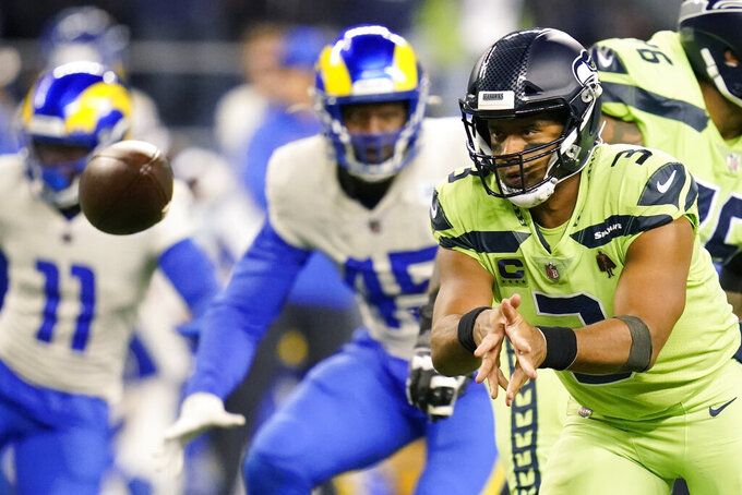 Seattle Seahawks quarterback Russell Wilson pitches out during the second half of an NFL football game against the Los Angeles Rams, Thursday, Oct. 7, 2021, in Seattle. (AP Photo/Elaine Thompson)