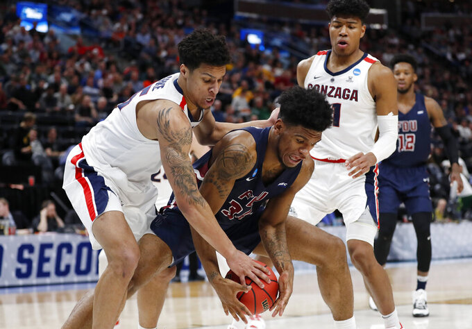 Fairleigh Dickinson forward Mike Holloway Jr. (34) loses control of the ball as he is defended by Gonzaga forward Brandon Clarke, left, and forward Rui Hachimura during a first-round game in the NCAA men's college basketball tournament Thursday, March 21, 2019, in Salt Lake City. (AP Photo/Jeff Swinger)