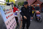 A security guard receives a sticker declaring he is vaccinated against the coronavirus at a stand promoting free shots outside an entrance to the Forbidden City in Beijing on Wednesday, April 14, 2021. China's success at controlling COVID-19 has resulted in a population that has seemed almost reluctant to get vaccinated. It is now accelerating its inoculation campaign by offering incentives — free eggs, store coupons and discounts on groceries and merchandise — to those getting a shot. (AP Photo/Ng Han Guan)