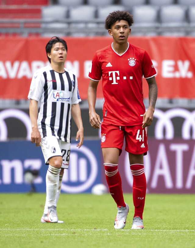 Munich's Chris Richards, right, and Freiburg's Changhoon Kwon from Freiburg are on the pitch during the German Bundesliga soccer match between Bayern Munich and SC Freiburg, Saturday, June 20, 2020. American defender Richards made his competitive debut for Bayern Munich, entering in the 84th minute of a 3-1 home win over Freiburg in the Bundesliga. (Sven Hoppe/dpa via AP)