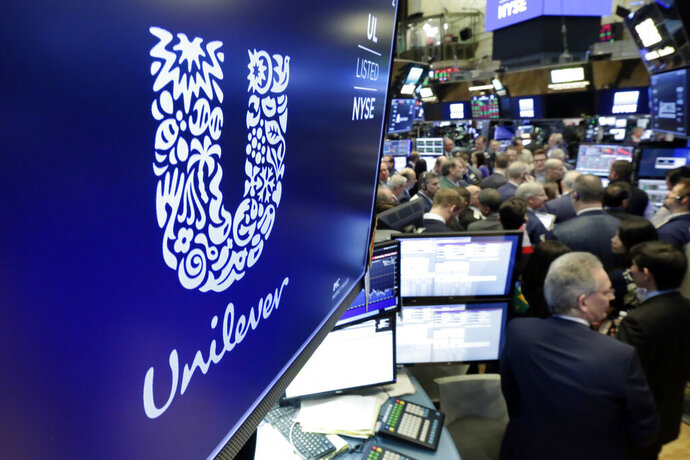 FILE - In this Thursday, March 15, 2018 file photo, the logo for Unilever appears above a trading post on the floor of the New York Stock Exchange. Consumer products giant Unilever, whose brands include Dove soaps and Lipton teas, said on Monday Oct. 7, 2019, they are pledging to halve its use of non-recycled plastics by 2025. (AP Photo/Richard Drew, File)