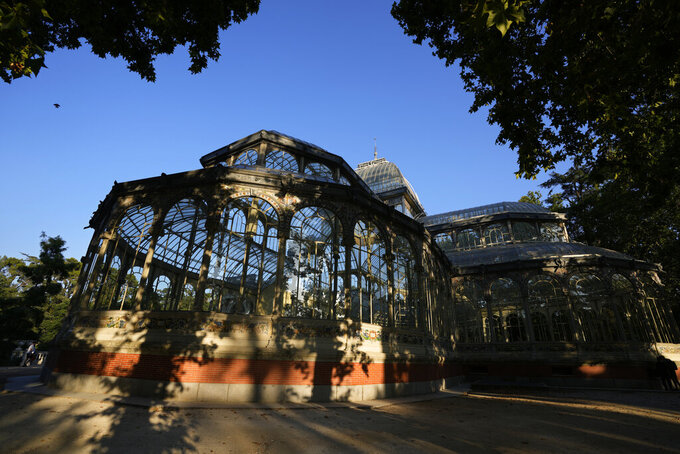 The Glass Palace stands shaded by trees in the Retiro park in Madrid, Spain, Thursday, July 22, 2021. Madrid's tree-lined Paseo del Prado boulevard and the adjoining Retiro park have been added to UNESCO's World Heritage list. The UNESCO World Heritage Committee backed the candidacy that highlighted the green area's introduction of nature into Spain's capital. (AP Photo/Paul White)