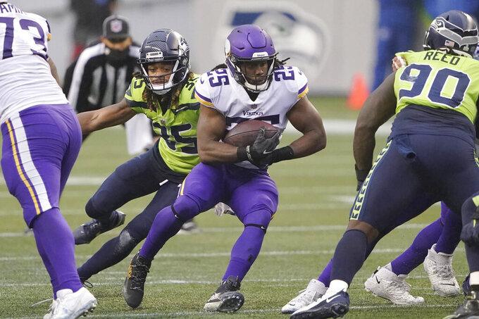 Minnesota Vikings' Alexander Mattison (25) is chased by Seattle Seahawks' Ryan Neal during the first half of an NFL football game, Sunday, Oct. 11, 2020, in Seattle. (AP Photo/Ted S. Warren)