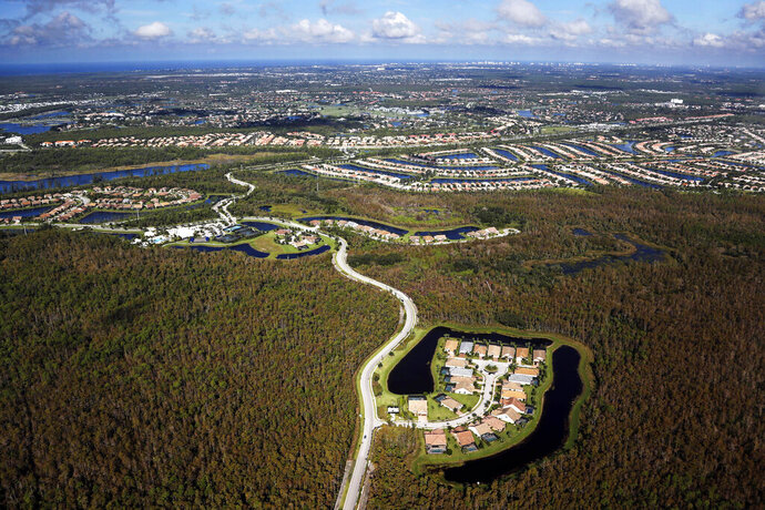 In this Thursday, Oct. 24, 2019, photo, a housing development built in Everglades wetlands is seen from the air near Naples, Florida. (AP Photo/Robert F. Bukaty)
