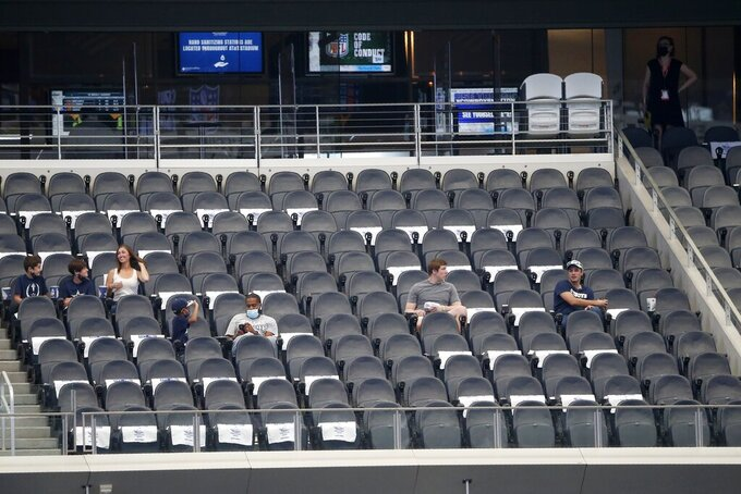 Fans watch the Dallas Cowboys and Atlanta Falcons warm up before an NFL football game in Arlington, Texas, Sunday, Sept. 20, 2020. (AP Photo/Michael Ainsworth)