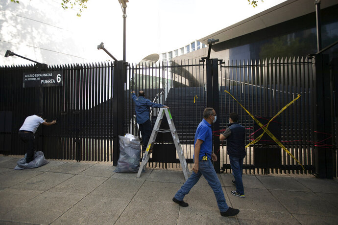 Senate workers remove posters and ribbons placed by demonstrators protesting against Mexican President Andres Manuel Lopez Obrador's effort to eliminate trust funds which he says are sources of corruption, at an entrance to the Senate in Mexico City, Wednesday, Oct. 21, 2020. The Senate passed various laws on Wednesday eliminating over 100 trusts which finance everything from science to movie productions to disaster relief. (AP Photo/Fernando Llano)