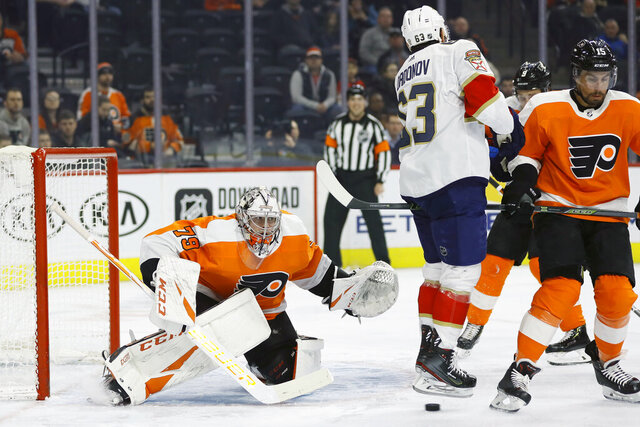 Philadelphia Flyers' Carter Hart (79) cannot stop a shot by Florida Panthers' MacKenzie Weegar as Evgenii Dadonov (63) and Philadelphia Flyers' Matt Niskanen (15) look on during the first period of an NHL hockey game, Monday, Feb. 10, 2020, in Philadelphia. (AP Photo/Matt Slocum)