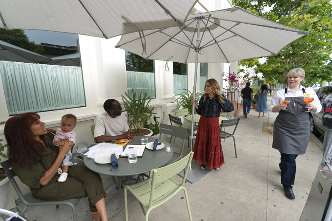 In this Saturday, June 19, 2021, photo, Caroline Styne, owner and wine director at The Lucques Group, standing under umbrella, welcomes back regular customers, Chris Anokute with his wife Jasmine and their 9-month-old son, Phoenix, at the A.O.C. Brentwood restaurant in Los Angeles. Styne has turned away dozens of customers at the company's A.O.C. West Hollywood restaurant because she doesn't have the staff to serve them, leaving seats empty. (AP Photo/Damian Dovarganes)