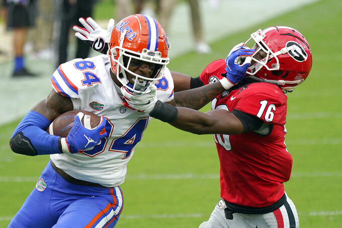 Florida tight end Kyle Pitts (84) tires to get past Georgia defensive back Lewis Cine (16) after a reception during the first half of an NCAA college football game, Saturday, Nov. 7, 2020, in Jacksonville, Fla. (AP Photo/John Raoux)