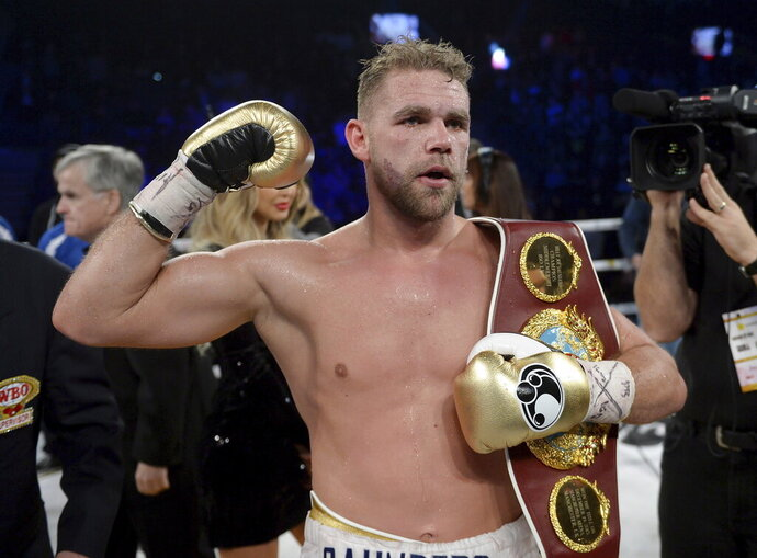"""FILE - In this Dec. 16, 2017, file photo, Billy Joe Saunders, of Britain, celebrates his win over David Lemieux, of Canada, to retain the WBO middleweight boxing title in Laval, Quebec. Saunders had his boxing license suspended Monday, March 30, 2020, after publishing a social media video in which he appeared to condone domestic violence amid the coronavirus outbreak. He has apologized for his remarks, saying: """"It was a silly mistake but I didn't mean to cause any harm to anyone and I certainly wouldn't promote domestic violence.""""(Ryan Remiorz/The Canadian Press via AP)"""