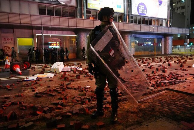 Police arrive on a street laid with bricks by protesters in Hong Kong, Wednesday, Jan. 1, 2020. Hong Kong toned down its New Year's celebrations amid the protests that began in June and which have dealt severe blows to the city's retail, tourism and nightlife sectors. (AP Photo/Vincent Yu)