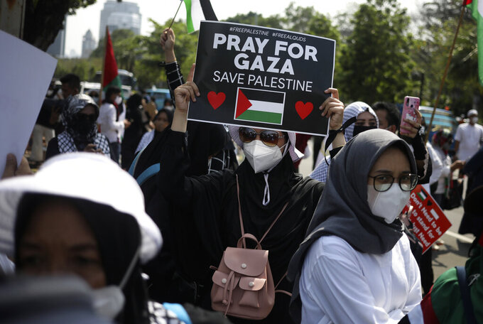 A Muslim woman holds up a poster during an anti-Israel rally outside the U.S. Embassy in Jakarta, Indonesia, Tuesday, May 18, 2021. Pro-Palestinian protesters marched to the heavily guarded U.S. Embassy in Indonesia's capital on Tuesday to demand an end to Israeli airstrikes in the Gaza Strip. (AP Photo/Dita Alangkara)