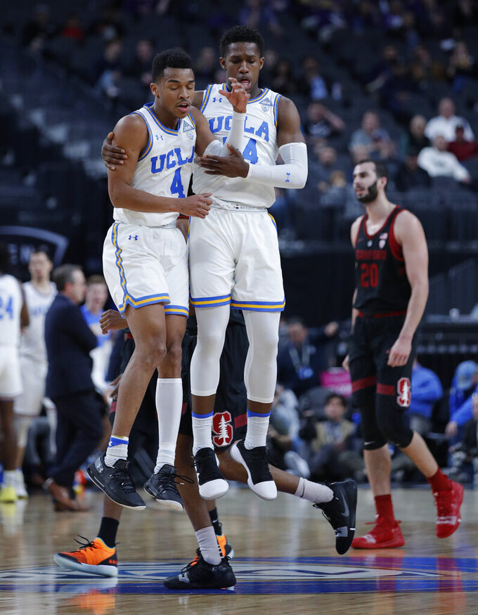 UCLA's Jaylen Hands, left, and David Singleton celebrate after a play against Stanford during the first half of an NCAA college basketball game in the first round of the Pac-12 men's tournament, Wednesday, March 13, 2019, in Las Vegas. (AP Photo/John Locher)