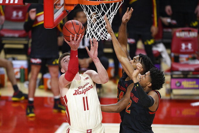 Wisconsin forward Micah Potter (11) goes to the basket against Maryland guard Aaron Wiggins (2) and forward Donta Scott, back, during the first half of an NCAA college basketball game Wednesday, Jan. 27, 2021, in College Park, Md. (AP Photo/Nick Wass)