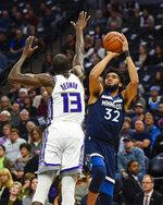 Minnesota Timberwolves center Karl-Anthony Towns(32) takes a shot over Sacramento Kings center DeWayne Dedmon during the first half of an NBA basketball game Monday, Jan. 27, 2020, in Minneapolis. (AP Photo/Craig Lassig)