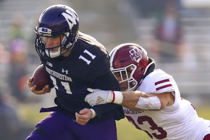 Northwestern's Aidan Smith, left, is tackled by Massachusetts's Mike Ruane during the first half of an NCAA college football game Saturday, Nov. 16, 2019, in Evanston, Ill. (AP Photo/Jim Young)