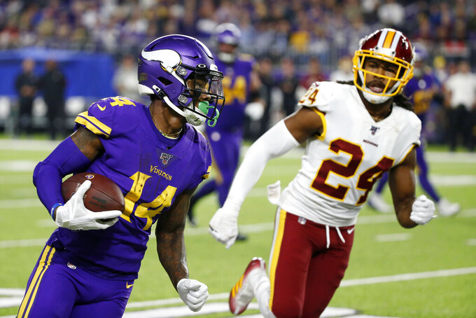 Minnesota Vikings wide receiver Stefon Diggs (14) runs from Washington Redskins cornerback Josh Norman (24) after catching a pass during the second half of an NFL football game, Thursday, Oct. 24, 2019, in Minneapolis. (AP Photo/Bruce Kluckhohn)