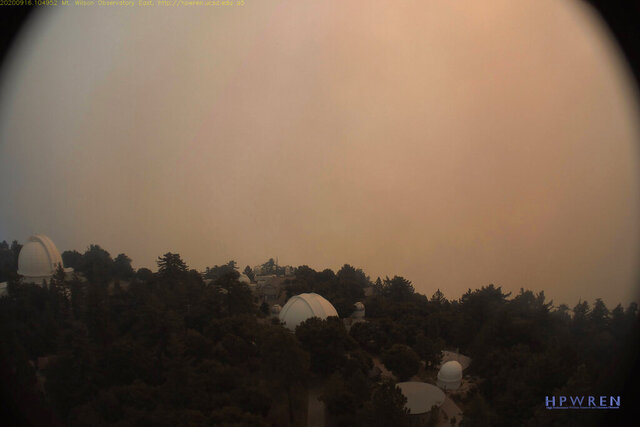 This photo provided by High Performance Wireless Research and Education Network (HPWREN) and ALERTWildfire from a camera atop Mount Wilson shows dense smoke shrouding the famed Southern California observatory Wednesday, Sept. 16, 2020. Firefighters have prevented the Bobcat wildfire from damaging the historic Mount Wilson Observatory.  Flames came within 500 feet of the observatory Tuesday, but a bulldozer line, burnout operations, water drops and brush clearance maintained there created protection, Angeles National Forest officials said in social media posts. (HPWREN/ALERTWildfire via AP)