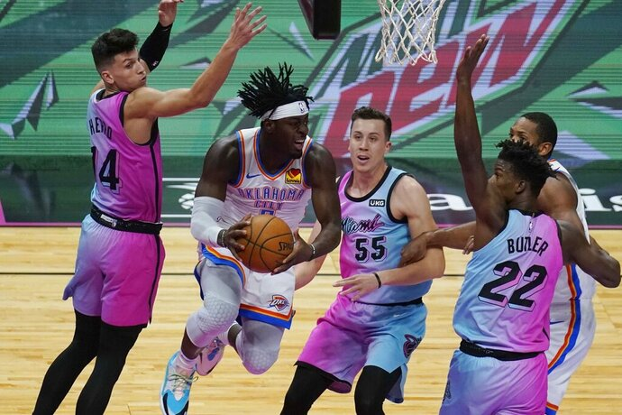 Oklahoma City Thunder guard Luguentz Dort (5) grabs a rebound surrounded by Miami Heat forward Duncan Robinson (55), forward Jimmy Butler (22) and guard Tyler Herro (14), during the first half of an NBA basketball game, Monday, Jan. 4, 2021, in Miami. (AP Photo/Marta Lavandier)