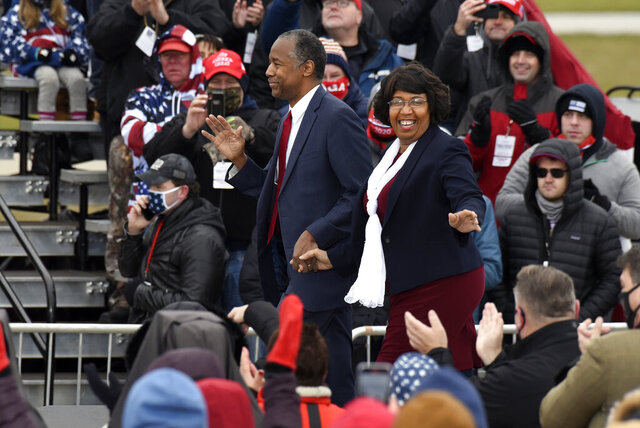 Housing and Urban Development Secretary Ben Carson, left, and his wife, Candy Carson, walk on stage at a campaign rally for President Donald Trump at Oakland County International Airport, Friday, Oct. 30, 2020, in Waterford Township, Mich. (AP Photo/Jose Juarez)