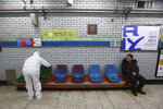 A worker wearing protective gears disinfect chairs as a precaution against the coronavirus at a subway station in Seoul, South Korea, Friday, Feb. 21, 2020. South Korea on Friday declared a