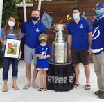 Christen, left, and Jim Gray, right, and son Declan , third from left, pose with the Stanley Cup with Tampa Bay Lightning players Steven Stamkos, second from left, and Ryan McDonagh, second from right, at the Children's Cancer Center in Tampa, Fla., on Oct. 16, 2020. Christen holds a framed picture of her youngest son, Finn, who died from Ewing's Sarcoma in January. The Lightning took the Stanley Cup to the Children's Cancer Center as part of their local tour of stops after winning the National Hockey League's championship trophy Sept. 28 in Edmonton, Alberta. ( Kristina Hjertkvist/Tampa Bay Lightning via AP)