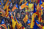 Pro independence demonstrators hold photos of imprisoned pro independence political leaders, during a demonstration in Barcelona, Spain, Saturday, Feb. 16, 2019.  Some thousands of Catalan separatists are marching in Barcelona to proclaim the innocence of 12 of their leaders who are on trial for their role in a failed 2017 secession bid. (AP Photo/Emilio Morenatti)