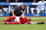 A trainer, top, checks on Cleveland Indians' Wilson Ramos who was injured during the seventh inning of a baseball game against the Boston Red Sox, Sunday, Aug. 29, 2021, in Cleveland. (AP Photo/Ron Schwane)