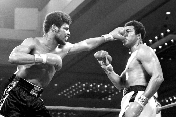 FILE- In this Feb. 15, 1978, file photo, the fist of challenger Leon Spinks flattens the nose of heavyweight champion Muhammad Ali during their title fight at Las Vegas. Former heavyweight champion Leon Spinks Jr. died Friday night, Feb. 5, 2021, after battling prostate and other cancers. He was 67. (AP Photo/File)