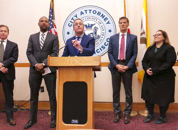 San Francisco City Attorney Dennis Herrera, at podium, announces that he's cracking down on the sale of e-cigarettes that he says aggressively target youth, at a City Hall news conference Tuesday, march 19, 2019. Legislation to be introduced would ban the sale of e-cigarettes anywhere in the city and county of San Francisco until the FDA has reviewed the product for sale. (AP Photo/Janie Har)