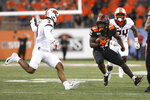 Oregon State running back Artavis Pierce (21) tries to avoid Oklahoma State safety Tre Sterling (3) during the first half of an NCAA college football game in Corvallis, Ore., Friday, Aug. 30, 2019. (AP Photo/Amanda Loman)