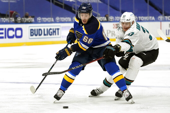 St. Louis Blues' Mike Hoffman (68) and San Jose Sharks' Fredrik Handemark (37) chase after a loose puck during the second period of an NHL hockey game Monday, Jan. 18, 2021, in St. Louis. (AP Photo/Jeff Roberson)