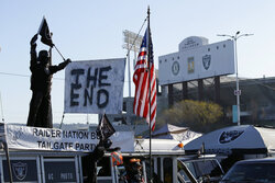 """A sign reads """"The End"""" on top of the Raider Nation Bus before the start of an NFL football between the Oakland Raiders and the Jacksonville Jaguars game in Oakland, Calif., Sunday, Dec. 15, 2019. The game is the final scheduled Raiders game in Oakland. (AP Photo/Eric Risberg)"""