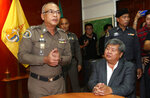 Thai business tycoon president of Italian-Thai Development Premchai Karnasuta, right, is seated after arriving at the wildlife police headquarters Bangkok, Thailand, Wednesday, March 14, 2018. Premchai, currently facing nine charges including illegal hunting in a wildlife sanctuary, was further charged with illegal possession of ivory, illegal possession of firearms and attempted bribery. (AP Photo/Sakchai Lalit)